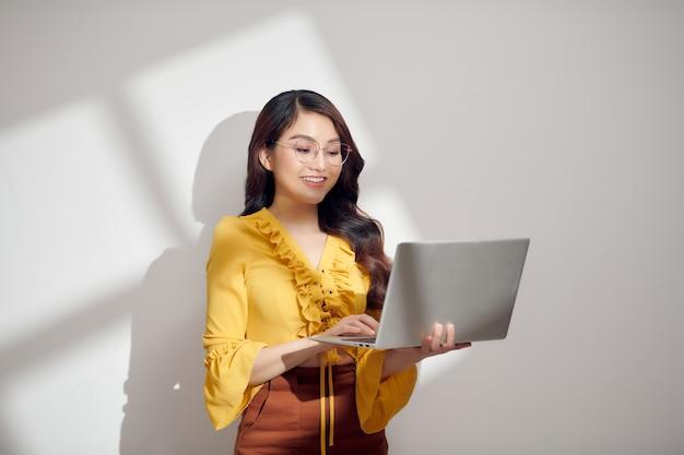 Retrato, de, un, sonriente, joven, rubio, mujer, tenencia, computadora portátil, aislado