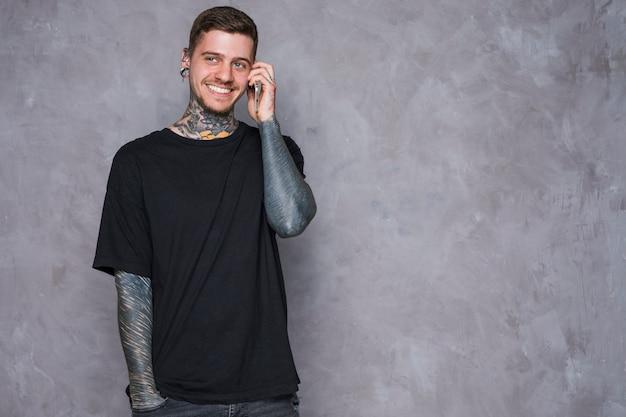 Retrato sonriente de un joven tatuado con orejas perforadas hablando por teléfono móvil