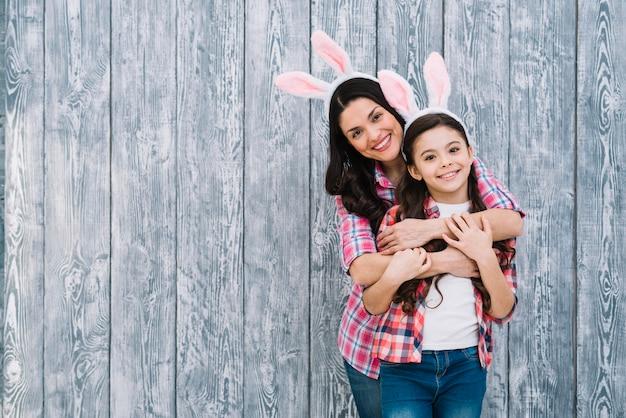 Retrato sonriente de madre abrazando a su hija por detrás frente a fondo de madera