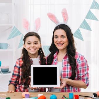 Retrato sonriente de madre e hija mostrando tableta digital detrás de la mesa de madera con huevos de pascua