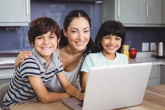 Retrato de sonriente madre e hijos usando una computadora portátil