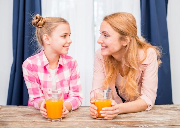 Retrato sonriente de una madre y su hija sosteniendo un vaso de jugo mirando el uno al otro en mesa de madera