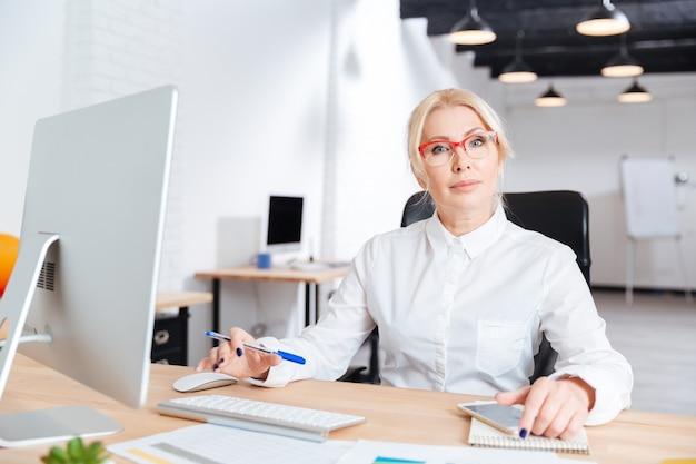 Retrato, de, un, sonriente, maduro, mujer de negocios, trabajando, en, oficina