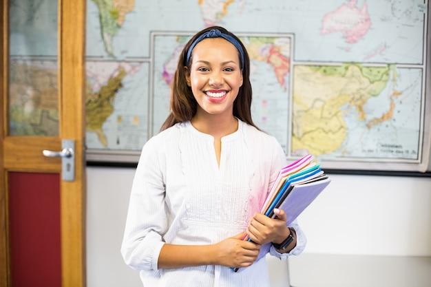 Retrato de sonriente maestro de escuela con libros en el aula