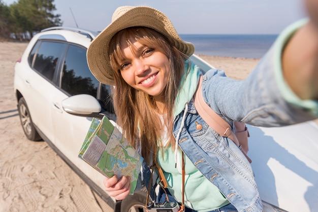 Retrato sonriente del mapa femenino de la tenencia del viajero en la mano que toma el selfie con su coche en la playa