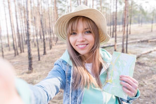 Retrato sonriente de un mapa de la tenencia de la muchacha a disposición que toma el selfie en el teléfono móvil