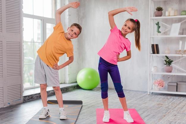 Retrato sonriente de una muchacha y de un muchacho que se colocan en estirar de la estera del ejercicio
