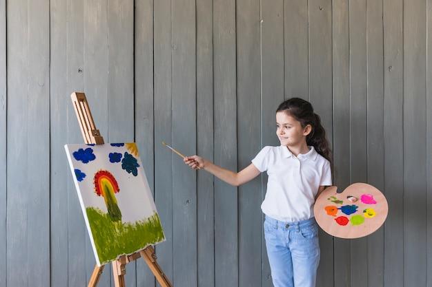 Retrato sonriente de una muchacha que se coloca delante del caballete que sostiene la brocha y la paleta