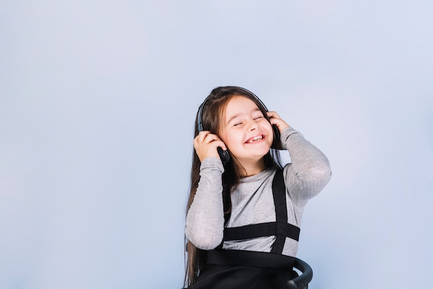 Retrato sonriente de una muchacha que disfruta de la música en el auricular contra fondo azul