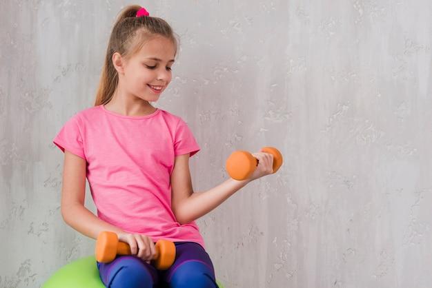 Retrato sonriente de una muchacha que ejercita con pesa de gimnasia contra la pared
