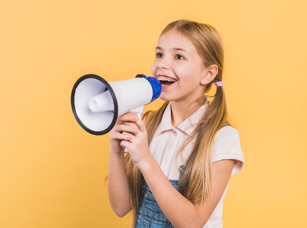Retrato sonriente de una muchacha que grita en el megáfono contra fondo amarillo