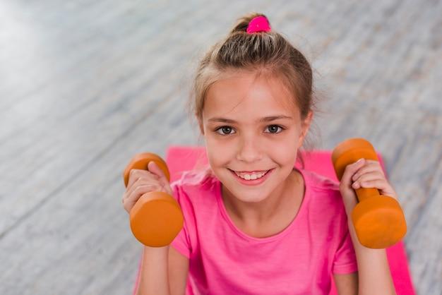 Retrato sonriente de una muchacha que hace ejercicio con pesa de gimnasia