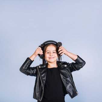 Retrato sonriente de una muchacha que lleva música que escucha de la chaqueta negra en el auricular