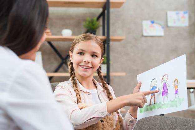Retrato sonriente de una muchacha que muestra el dibujo de la familia a su psicólogo de sexo femenino