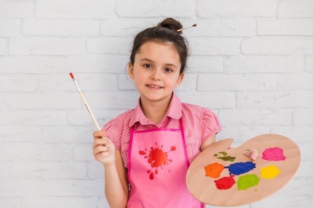 Retrato sonriente de una muchacha que se opone a la pared de ladrillo blanca que sostiene la brocha y la paleta colorida