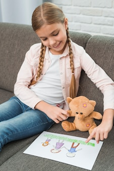 Retrato sonriente de una muchacha que se sienta en el sofá que muestra el dibujo de la familia al oso de peluche