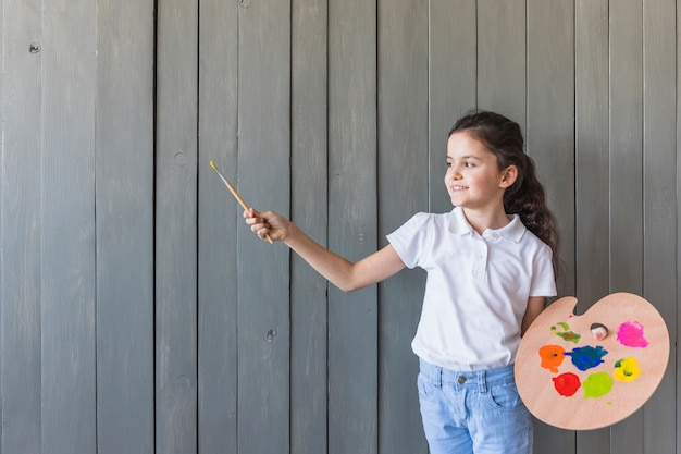 Retrato sonriente de una muchacha que sostiene el pincel y la paleta en la mano que se opone a la pared de madera gris