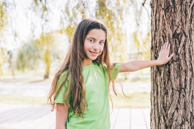Retrato sonriente de una muchacha que toca su mano en tronco de árbol
