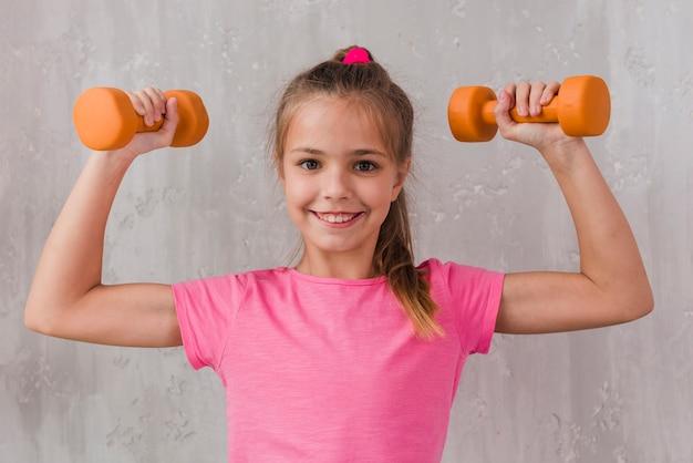 Retrato sonriente de una muchacha rubia que dobla su músculo que lleva a cabo pesa de gimnasia en manos contra el contexto concreto
