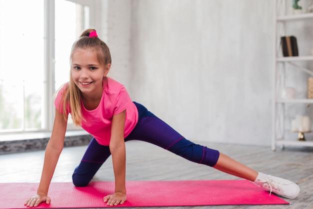Retrato sonriente de una muchacha rubia que ejercita en la estera rosada