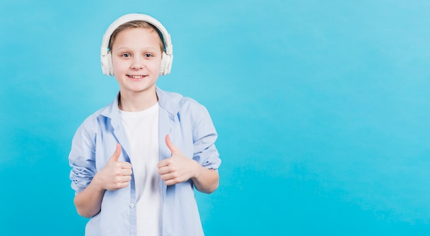 Retrato sonriente de un muchacho con el auricular blanco en su cabeza que muestra el pulgar encima de la muestra contra el contexto azul