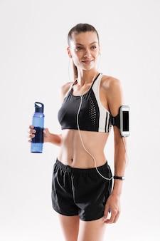 Retrato de una sonriente mujer atractiva fitness en auriculares