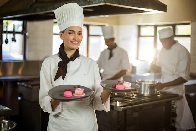 Retrato de sonriente mujer chef presentando platos de postre