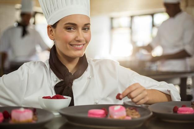 Retrato de sonriente mujer chef terminando platos de postre