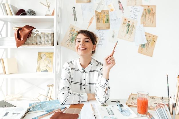 Retrato de una sonriente mujer diseñadora de moda con pincel