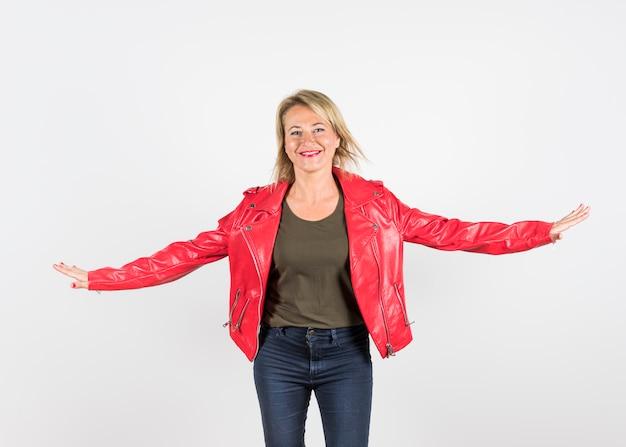 Retrato sonriente de una mujer elegante en chaqueta de cuero roja contra el fondo blanco