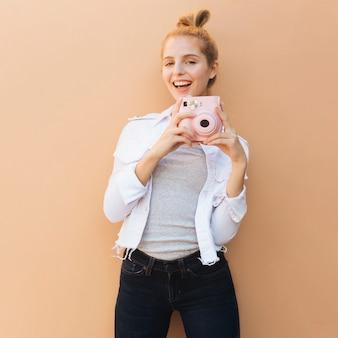 Retrato sonriente de una mujer hermosa joven que sostiene la cámara instantánea rosada contra el contexto beige