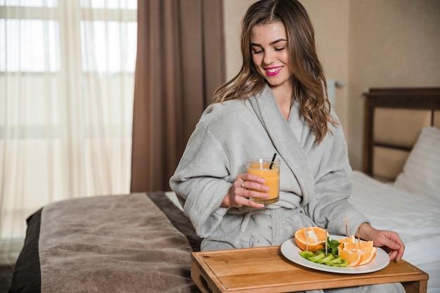 Retrato sonriente de una mujer joven en la bata de baño que se sienta en la cama que desayuna sano fresco