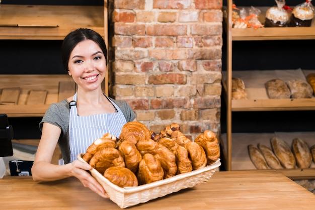Retrato sonriente de una mujer joven con una cesta de croissant recién horneada en la panadería