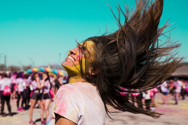 Retrato sonriente de una mujer joven con color holi sacudiendo su cabello