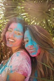 Retrato sonriente de una mujer joven con color holi en su cara mirando a cámara