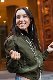 Retrato sonriente de una mujer joven disfrutando mientras escucha música en el teléfono