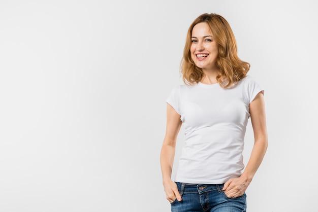 Retrato sonriente de una mujer joven con las manos en su bolsillo mirando a la cámara