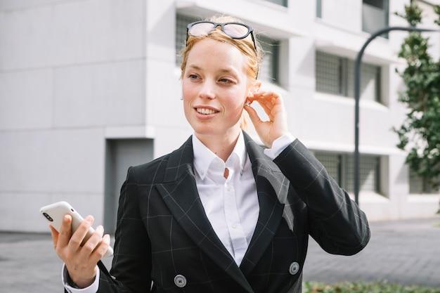 Retrato sonriente de una mujer joven que ajusta el bluetooth que sostiene el teléfono móvil en la mano