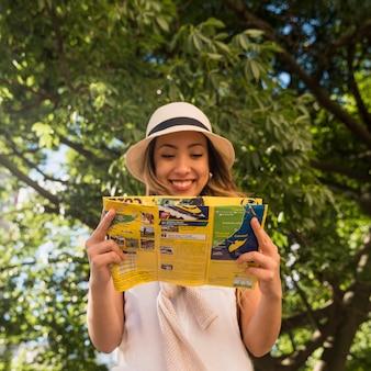 Retrato sonriente de la mujer joven que se coloca en el mapa de la lectura del parque