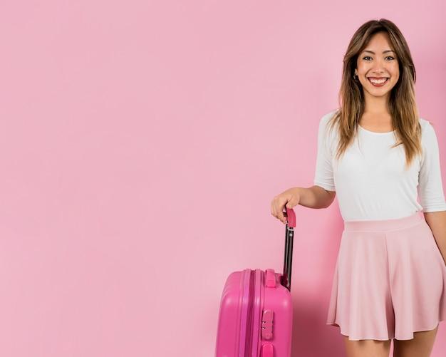 Retrato sonriente de la mujer joven que se coloca con su bolso del equipaje contra fondo rosado