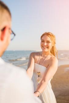Retrato sonriente de una mujer joven que lleva a cabo las manos de su novio que goza en la playa