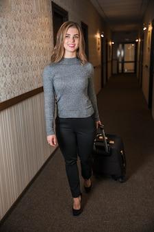 Retrato sonriente de una mujer joven que lleva la maleta caminando en el pasillo del hotel