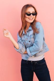 Retrato sonriente de una mujer joven que llevan las gafas de sol contra el contexto rosado