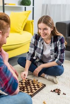 Retrato sonriente de la mujer joven que se sienta con su novio que juega a ajedrez en casa