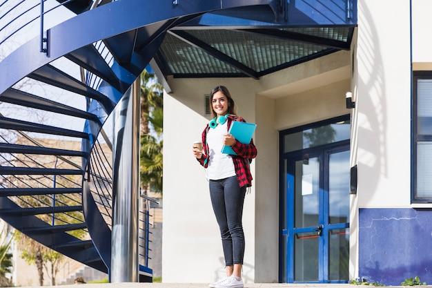 Retrato sonriente de una mujer joven que sostiene los libros y la taza de café para llevar que se coloca delante del edificio de la universidad