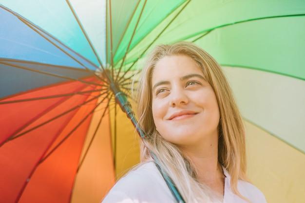 Retrato sonriente de una mujer joven que sostiene el paraguas colorido