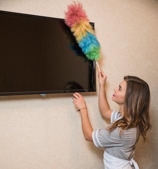 Retrato sonriente de una mujer joven que usa un plumero para limpiar la pantalla de televisión en la pared