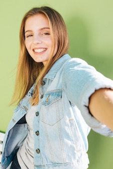 Retrato sonriente de una mujer joven rubia contra el contexto verde
