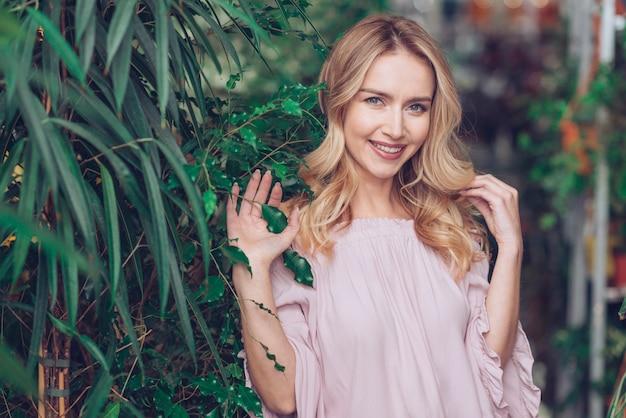 Retrato sonriente de una mujer joven rubia que se coloca cerca de las plantas verdes