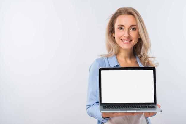 Retrato sonriente de una mujer joven rubia que muestra el ordenador portátil con la exhibición en blanco en su mano